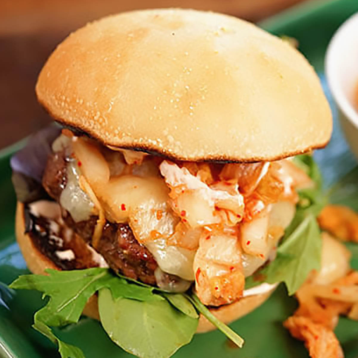 Kimchi Burger grilled and topped with slaw and cheese.