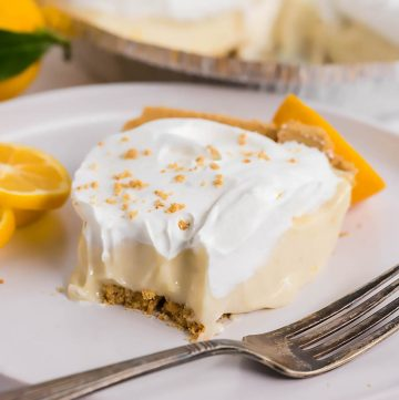 Lemon Icebox Pie on plate with fork. It's garnished with whipped cream and graham cracker crumbs.