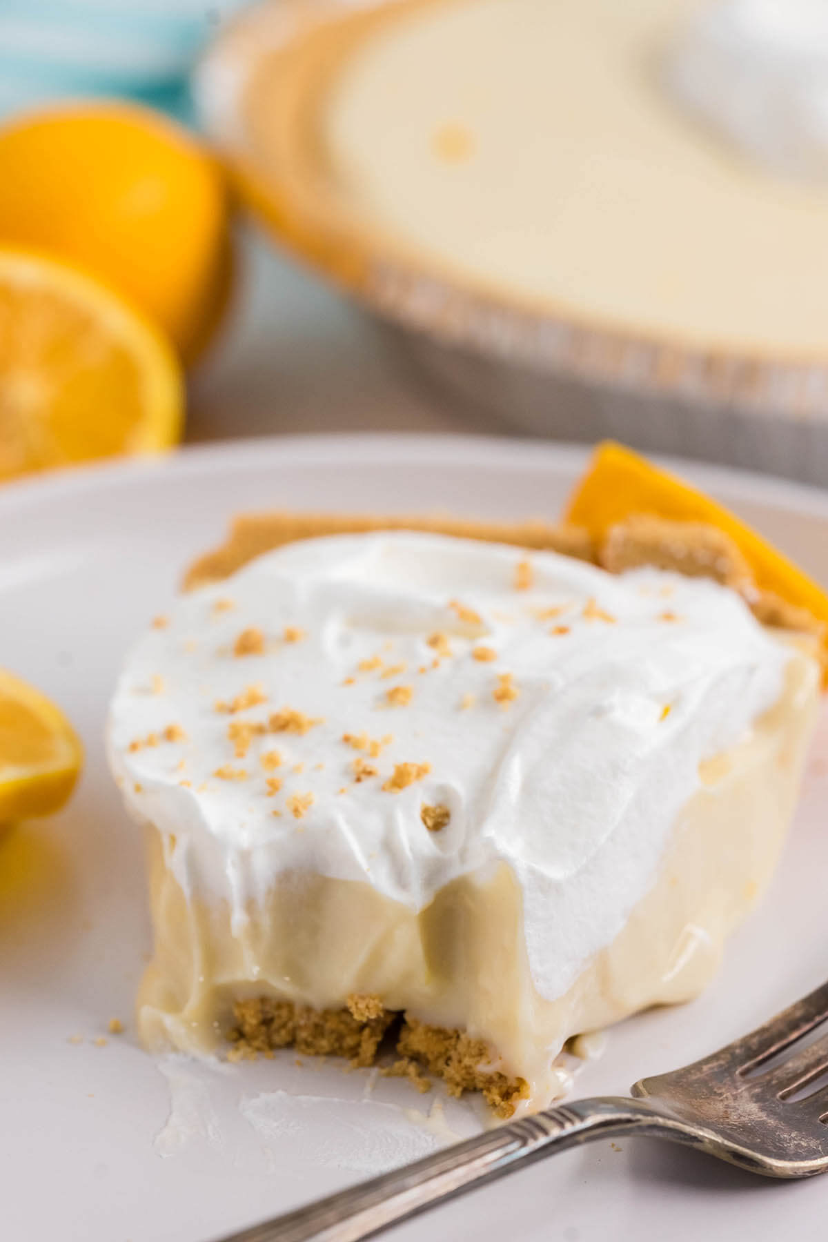 A close up photo of a slice of lemon icebox pie with bite taken out of it.