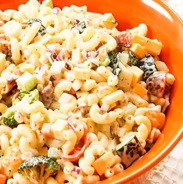 Creamy macaroni pasta salad in orange bowl.
