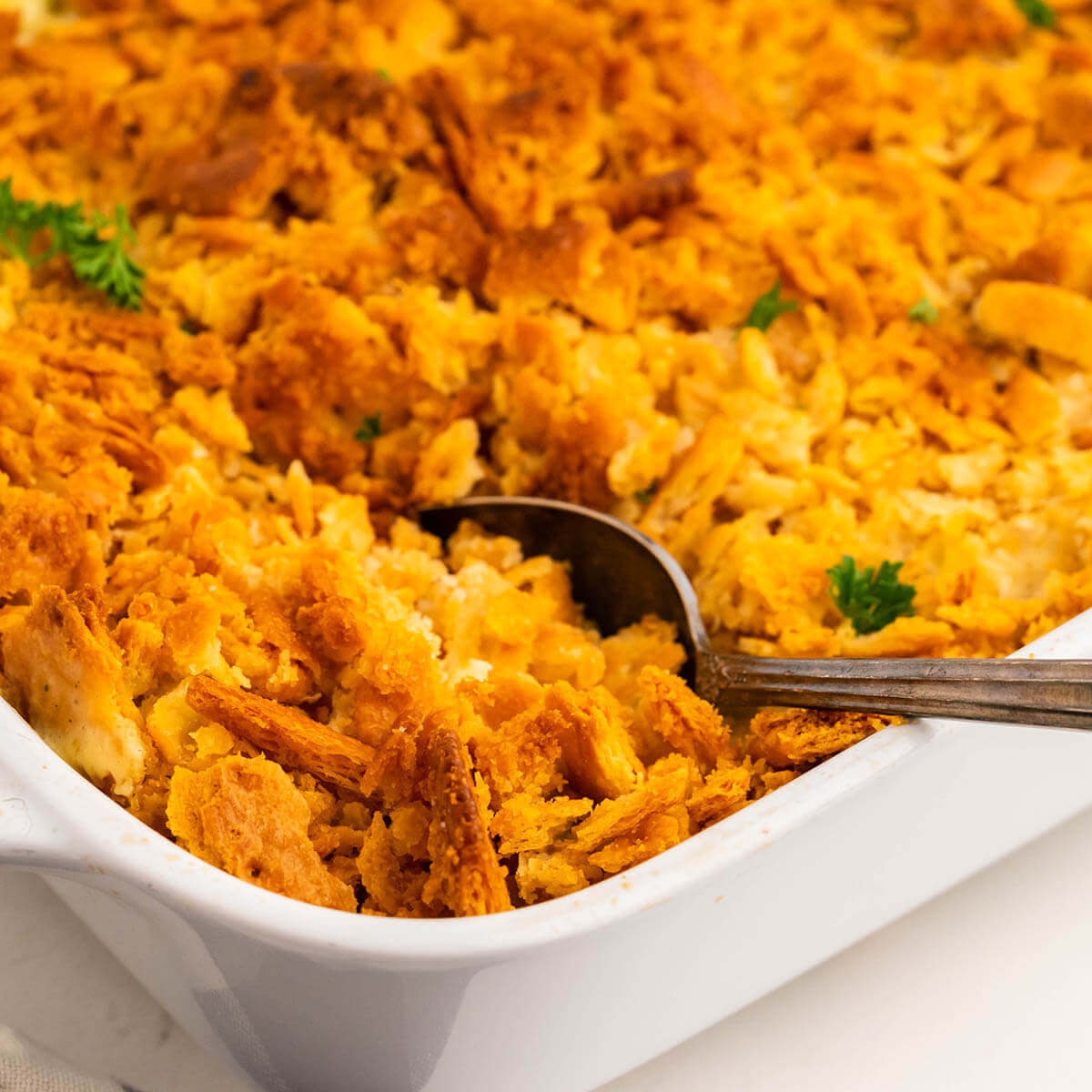 Ritzy chicken casserole in dish with serving spoon.