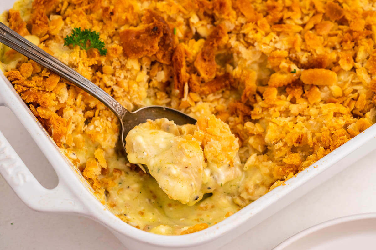 Casserole dish filled with creamy chicken mixture, topped with crispy crackers.