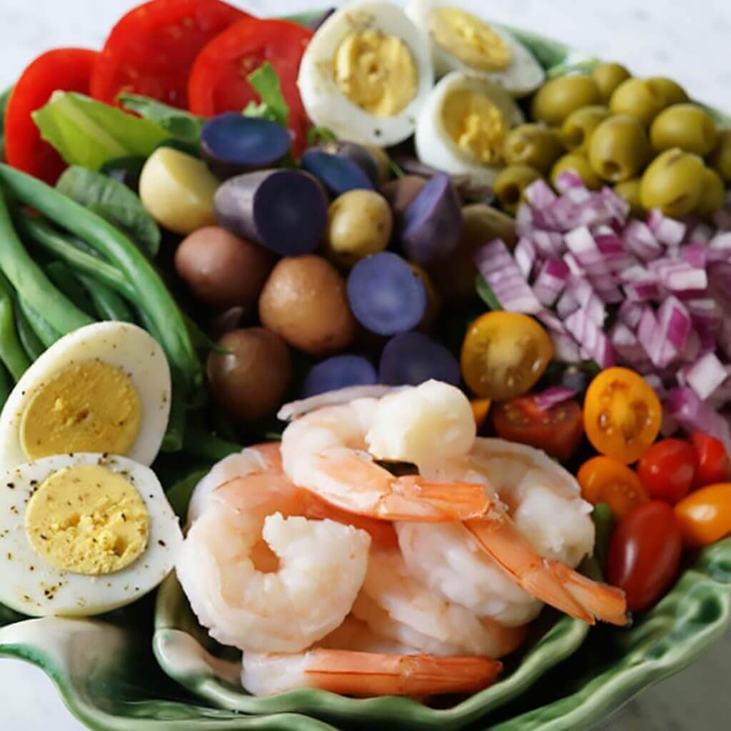 Large Shrimp Nicoise Salad filled with shrimp, eggs, green beans, potatoes and tomatoes.