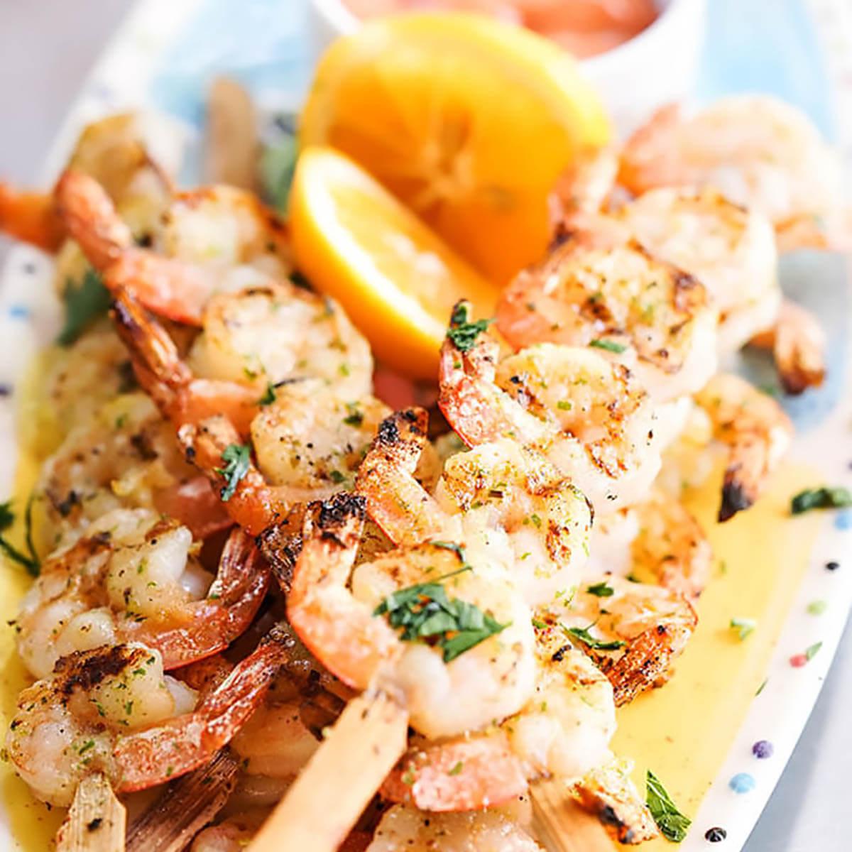Grilled Shrimp Skewers on platter with lemon.