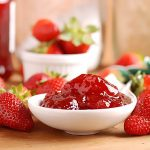 Strawberry jam in a white bowl surrounded by fresh strawberries.