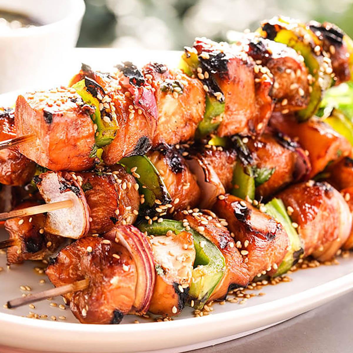 A platter filled with grilled teriyaki chicken kabobs sprinkled with sesame seeds for garnish.