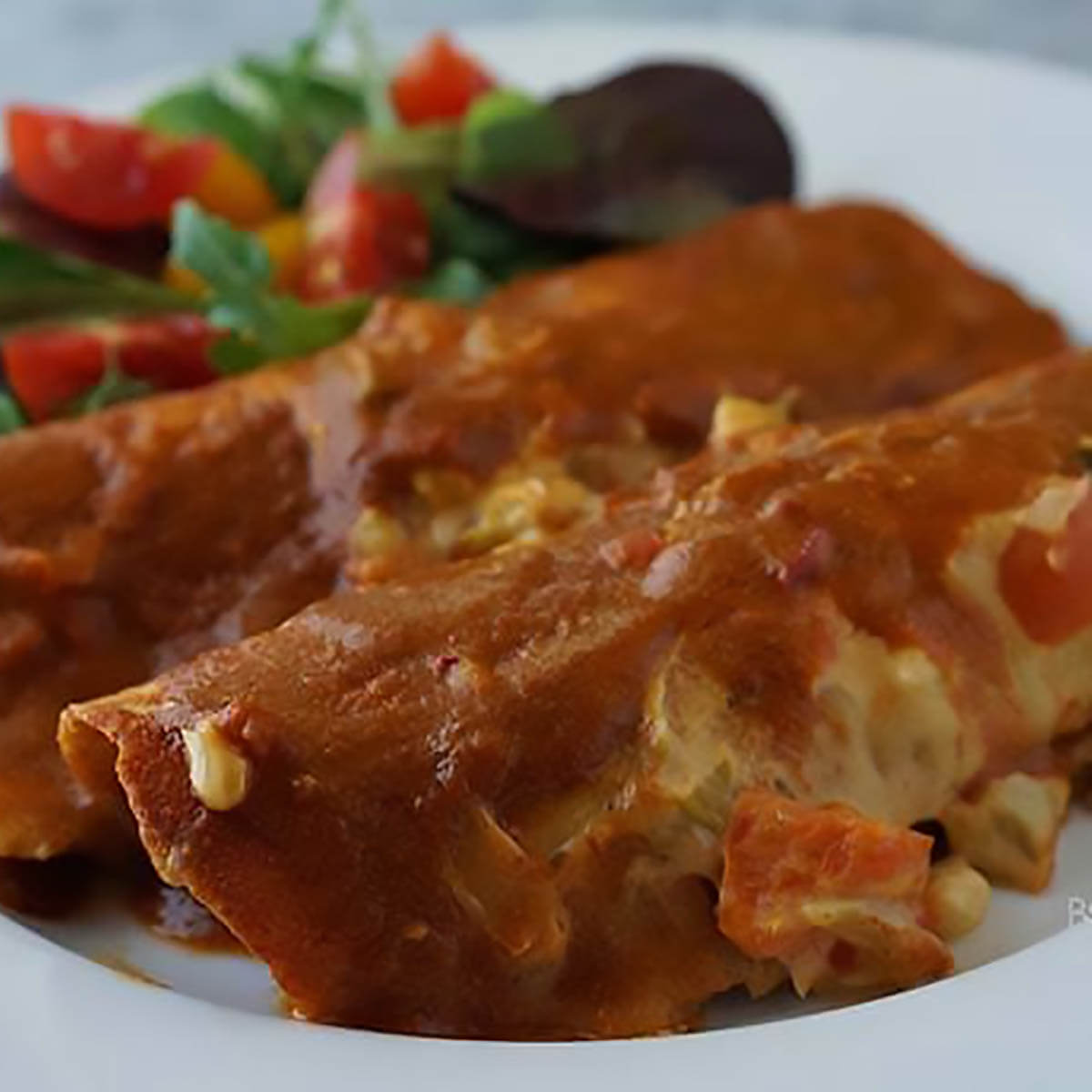 Enchiladas with red sauce on plate with salad.