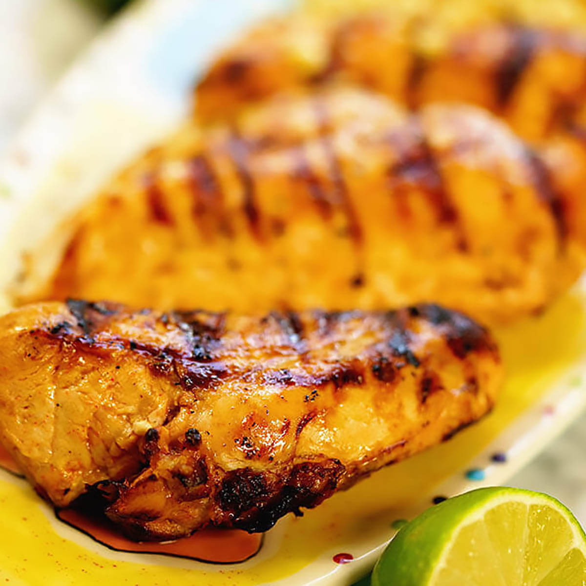 Grilled Chili Lime Chicken on platter served with a wedge of lime.
