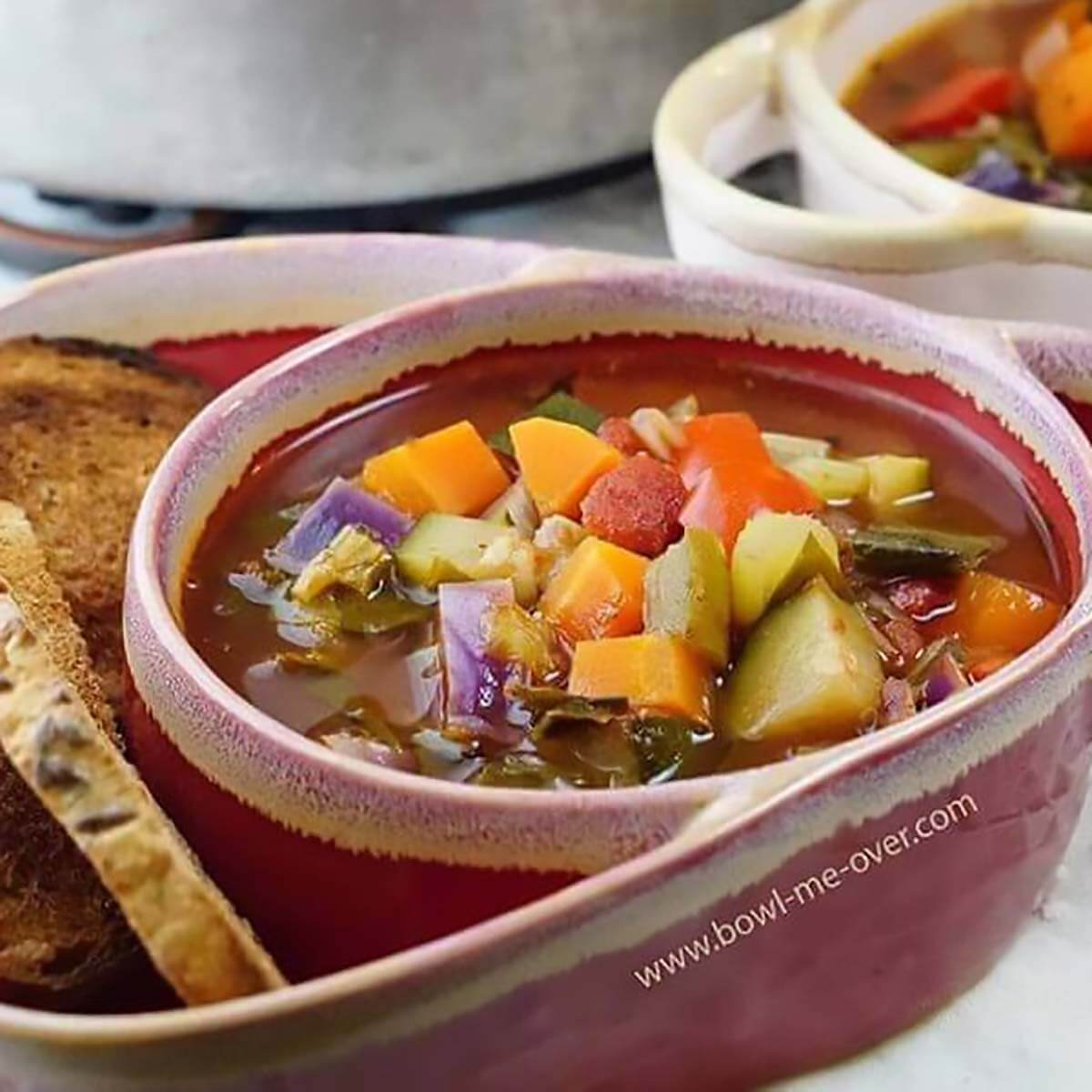 Minestrone soup in bowl served with toast points.