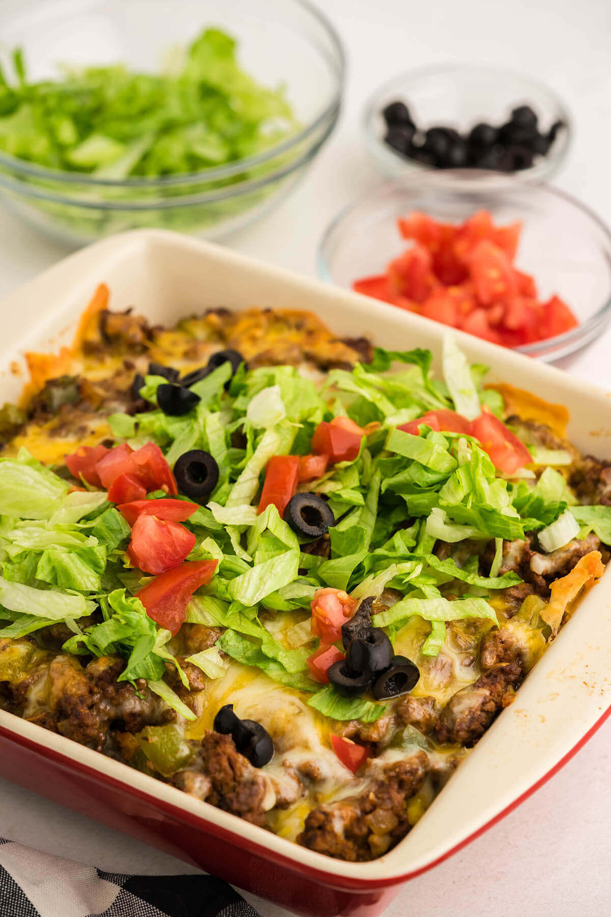 Taco Salad Casserole topped with shredded lettuce, tomatoes and olives.