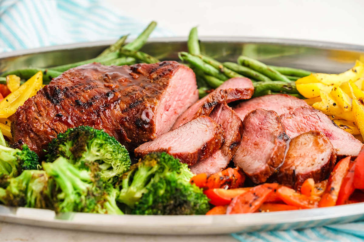 Platter of BBQ Tri Tip, surrounded by grilled vegetables.