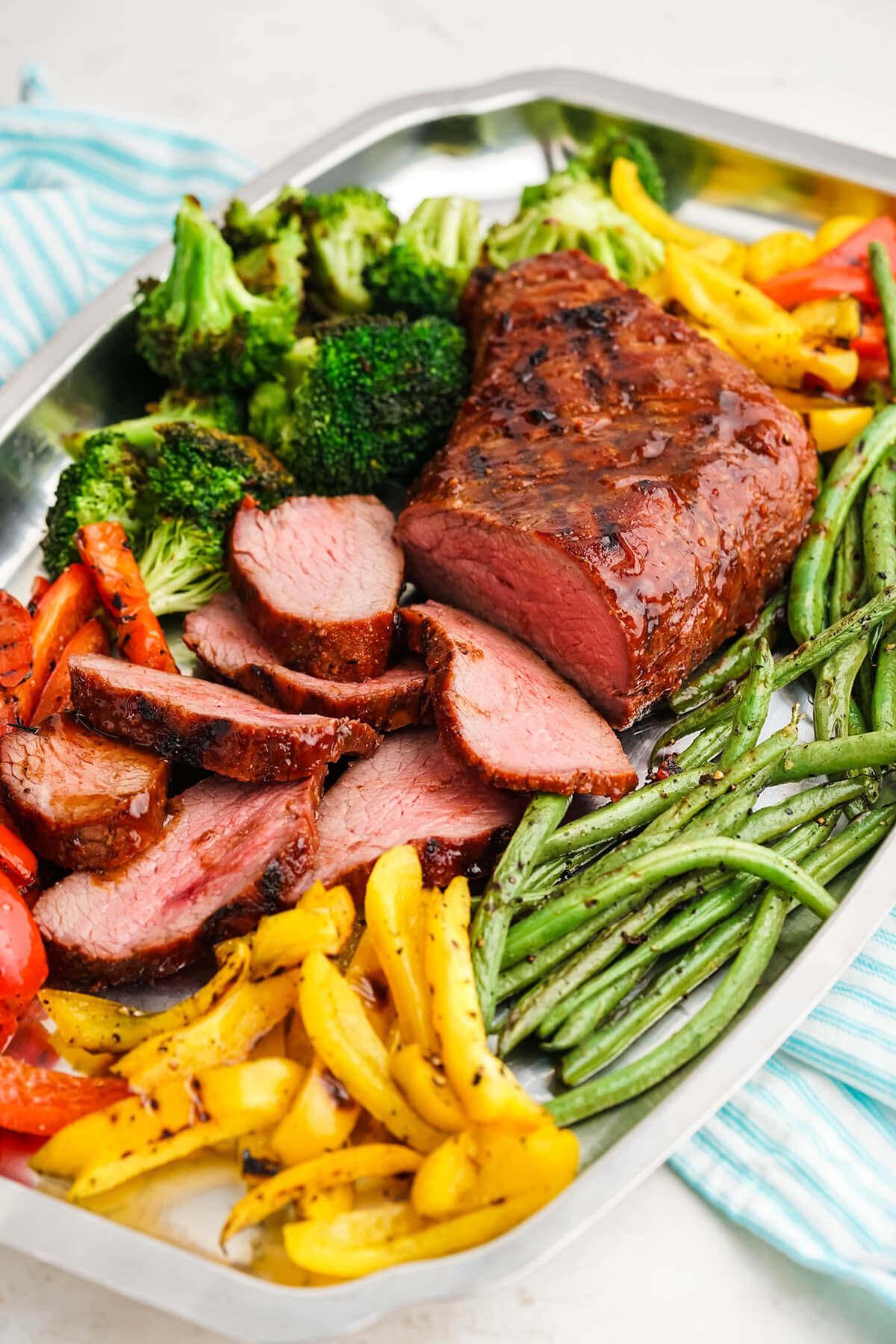 Sliced grilled steak on platter surrounded by grilled vegetables.