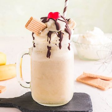 Banana Milkshake with drizzled chocolate, whipped cream and wafers, topped with a cherry.