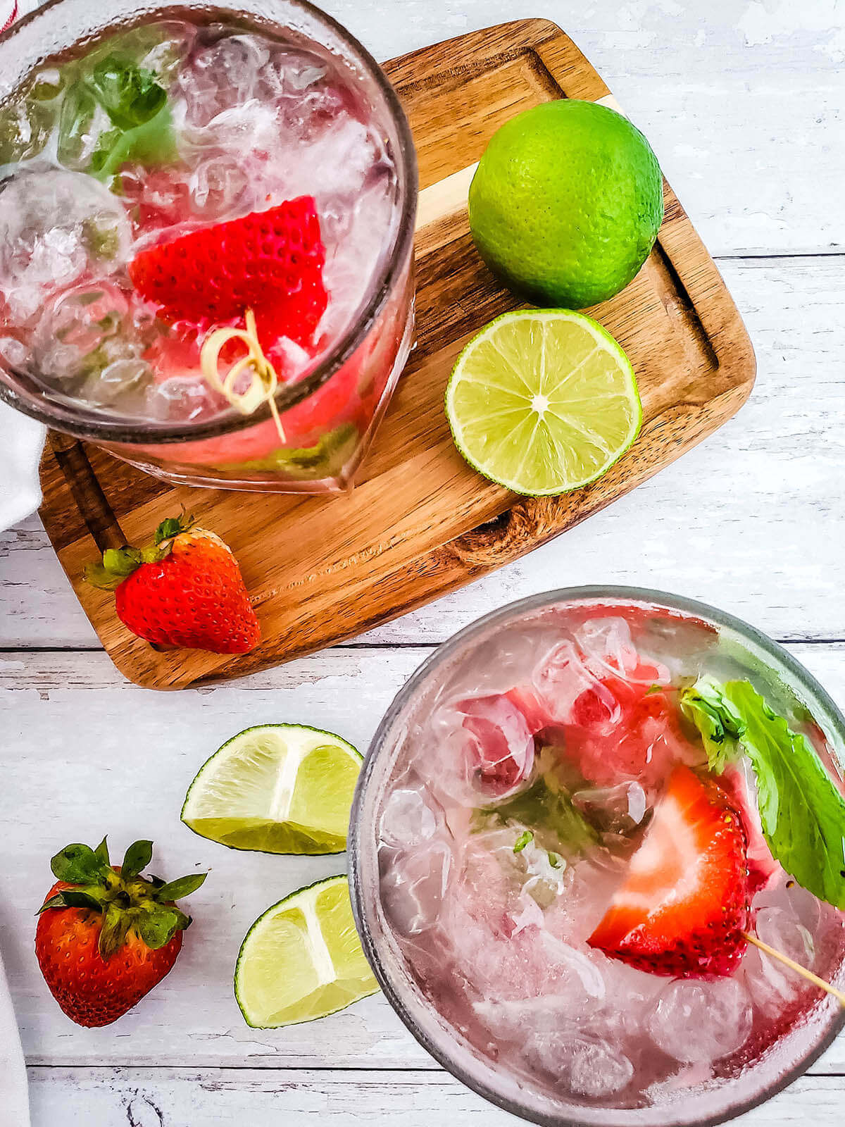 Overhead shot of two cocktail garnished with strawberries and lime.
