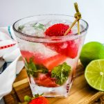Strawberry Mint Mojito with white rum garnished with lime and strawberry.