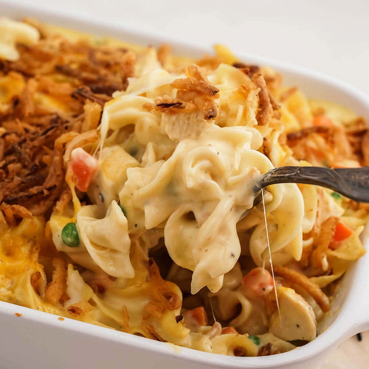 Chicken Noodle Casserole in pan with spoon scooping a serving.