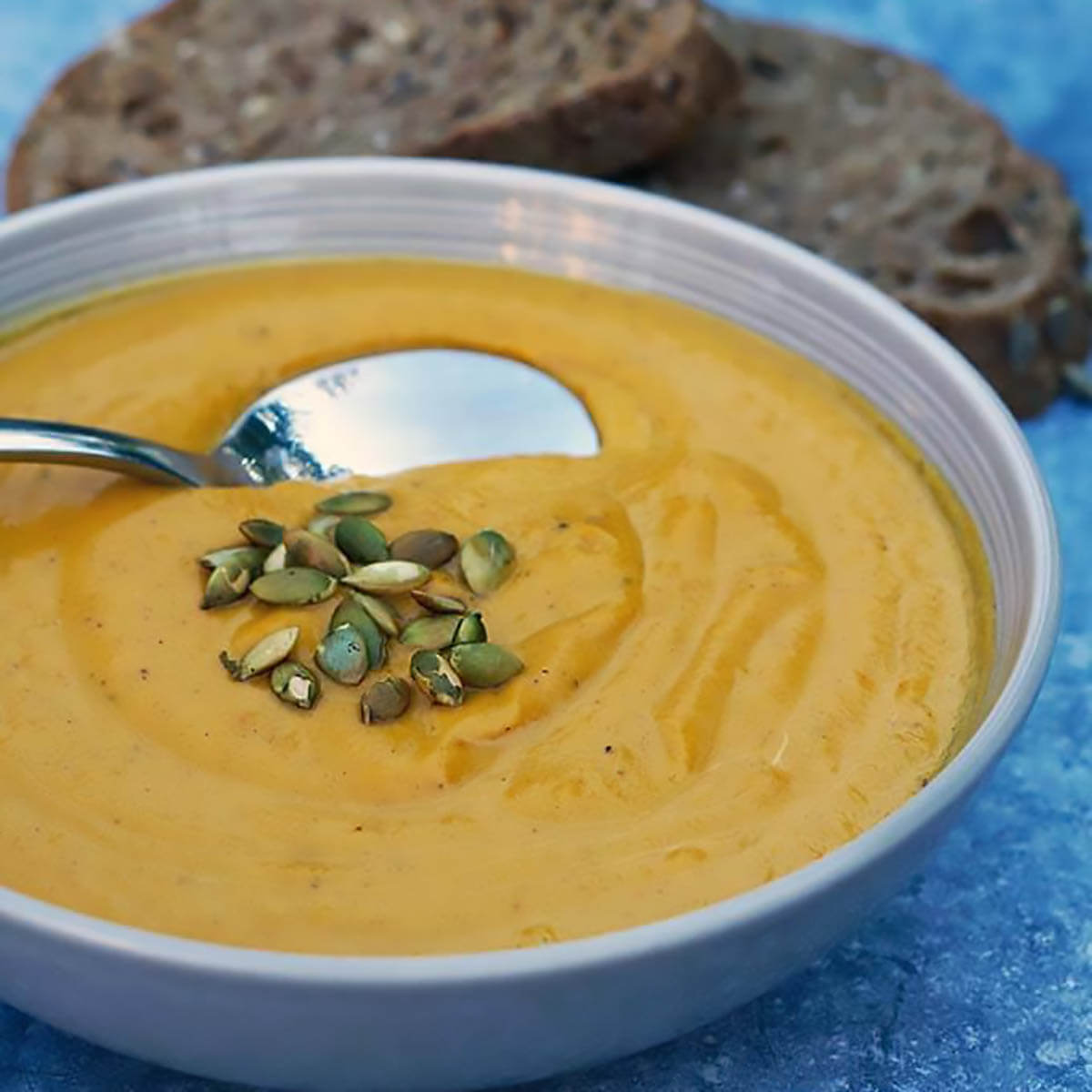 Butternut Squash Soup in bowl topped with pumpkin seeds and served with bread.