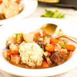 Beef stew with dumplings in white bowl with spoon.