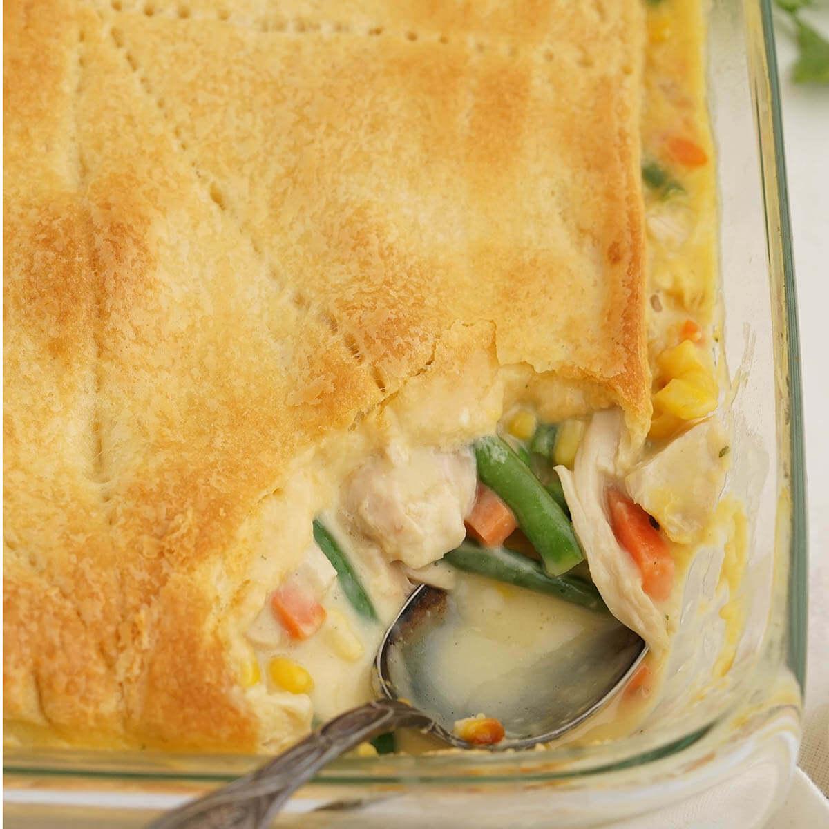 Chicken Pot Pie in Casserole dish with serving spoon.