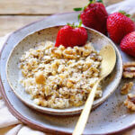 Oatmeal in bowl with spoon, served with strawberries.